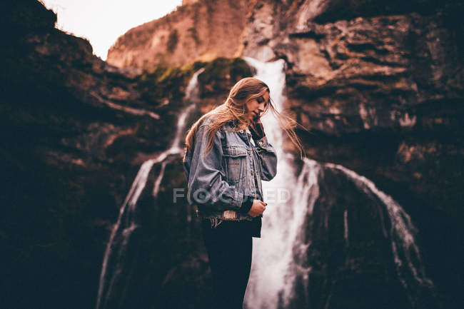Beautiful woman near picturesque waterfall — Stock Photo
