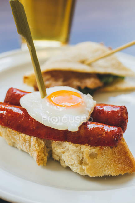 Fried egg with sausages on bread — Stock Photo
