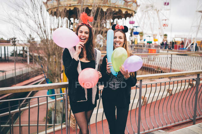 Ragazze sorridenti in maschere che tiene i palloni — Foto stock