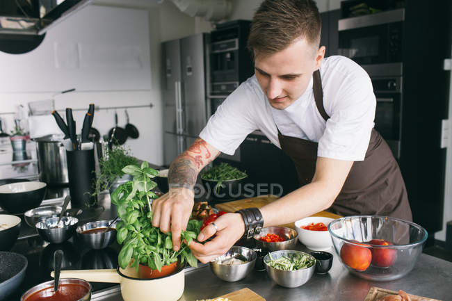Student in apron cutting basil leaves — Stock Photo