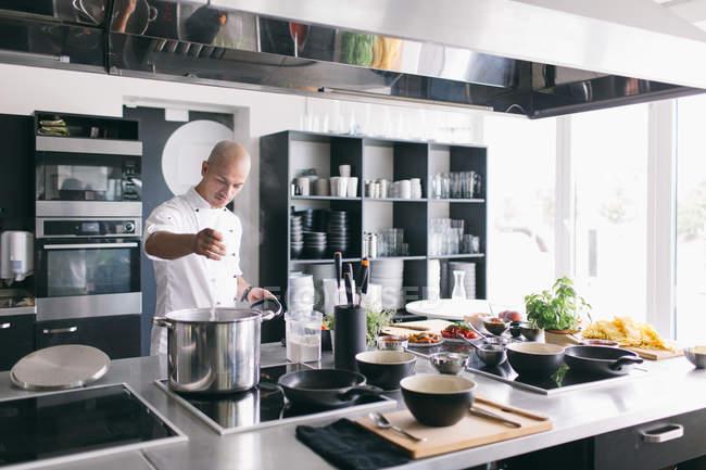 Profissional preparando comida na cozinha — Fotografia de Stock