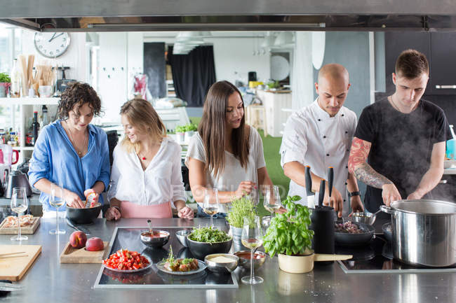 Друзья говорят и приготовление пищи в кухне — стоковое фото