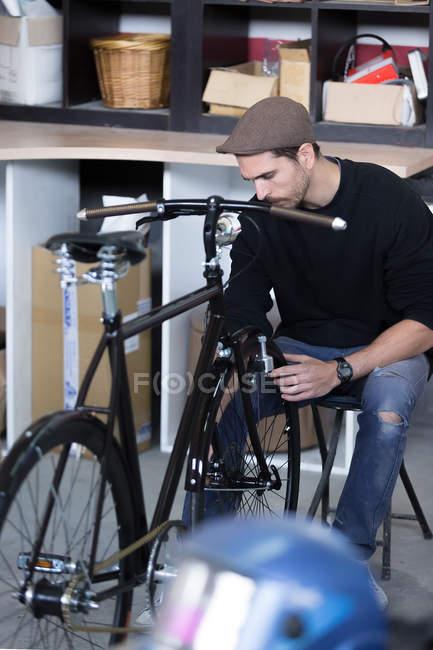 Man in cap taking measurements of bike — Stock Photo