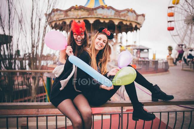 Ragazze sorridenti in maschere che tengono palloncini — Foto stock