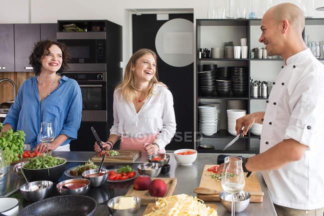 Fröhliche Frauen und Koch in der Küche — Stockfoto
