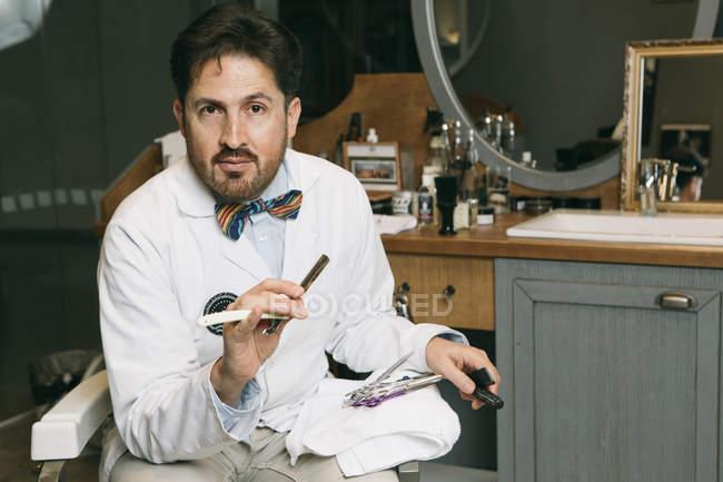 Мужской парикмахер сидя с лезвием и расческа — стоковое фото