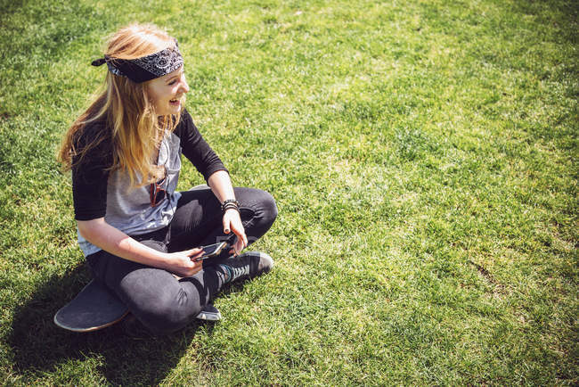 Skateboarder listening music in park — Stock Photo