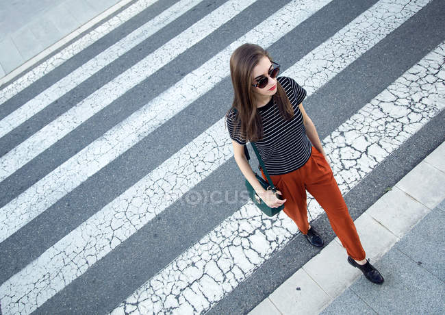 Young woman on crosswalk — Stock Photo