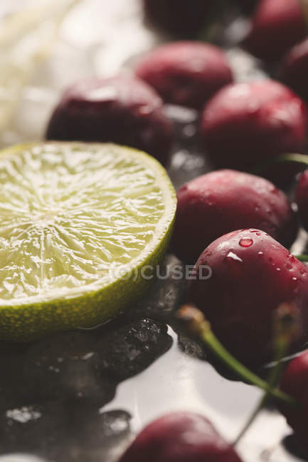 Red cherries and lime half — Stock Photo