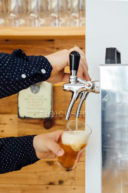 Hands pouring craft beer in glass — Stock Photo