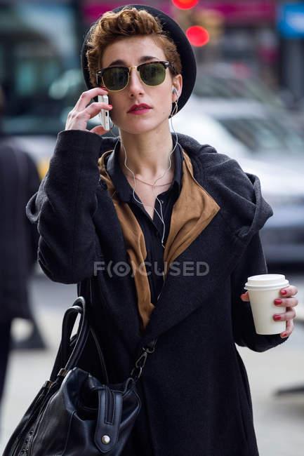 Молодий красивою жінкою із мобільного телефону і кава. — стокове фото