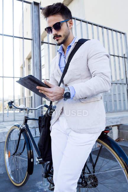 Giovane uomo d'affari in piedi con bicicletta — Foto stock