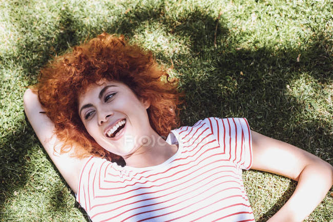 Mulher deitada na grama e rindo — Fotografia de Stock