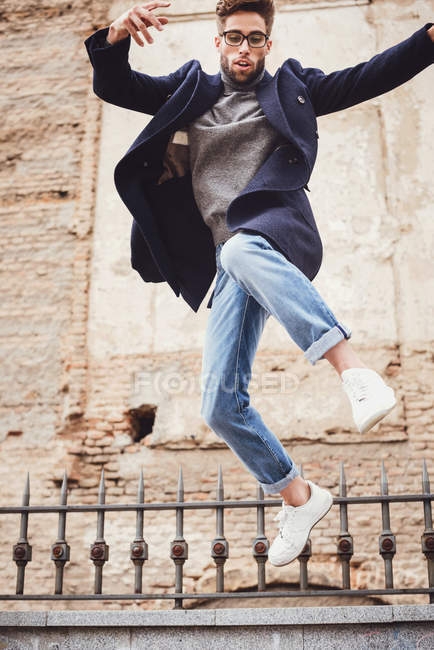 Trendy man with coat jumping — Stock Photo