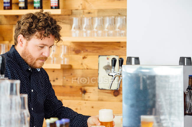Man holding glass with froth beer — Stock Photo