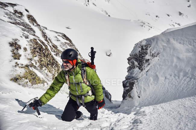 Homem subir na montanha de neve — Fotografia de Stock