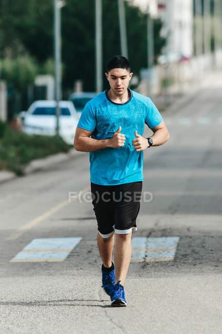 Спортсмен вздовж дороги міста — стокове фото