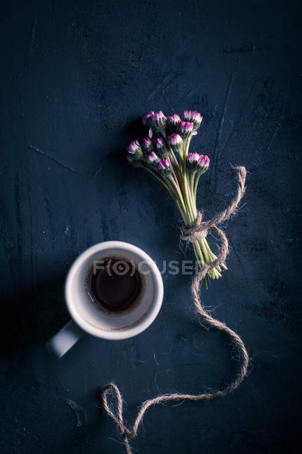 Bouquet of violet flowers and cup — Stock Photo