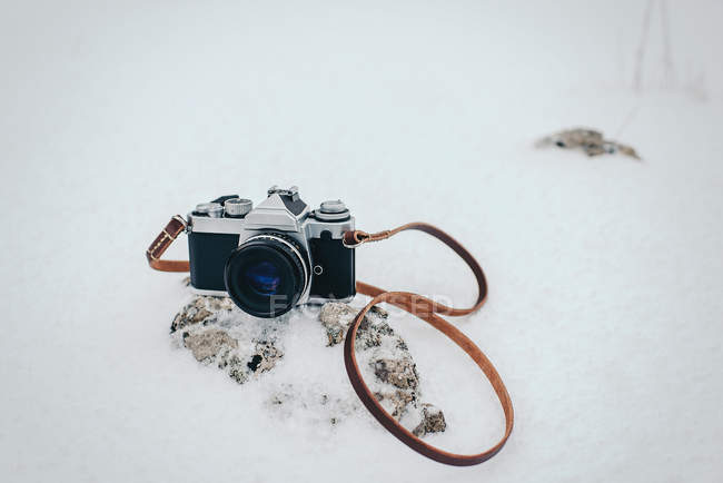 Vintage film camera on rock in snow — Stock Photo