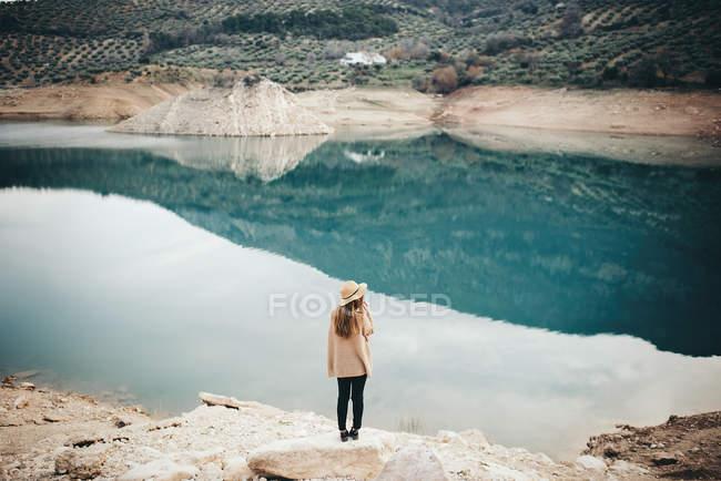 Visão traseira da mulher loira em chapéu no lago — Fotografia de Stock