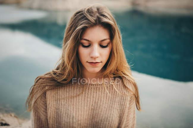 Menina loira bonita contra a superfície da água — Fotografia de Stock