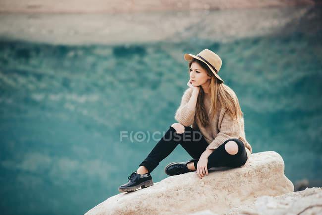 Chica bonita está sentada en piedra . - foto de stock