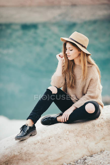 Pretty girl is sitting on stone. — Stock Photo