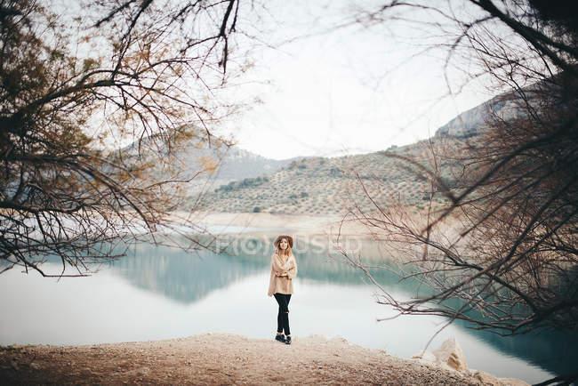 Женщина в шляпе против горного озера — стоковое фото