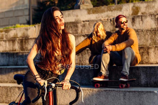 Fille avec vélo sur couple assis — Photo de stock