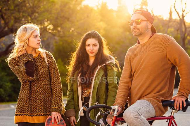 Zwei Mädchen und ein Mann auf dem Fahrrad im Sonnenuntergang — Stockfoto