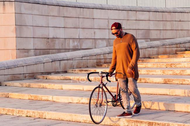 Homme descendant les escaliers à vélo — Photo de stock