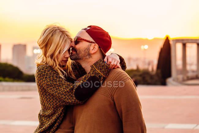 Пара обнимающихся на городском закате — стоковое фото