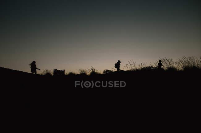 Trois silhouettes sur la colline — Photo de stock