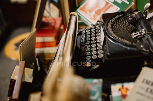 Vintage typewriter in pile of books — Stock Photo