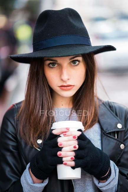 Молодая женщина держит чашку кофе — стоковое фото