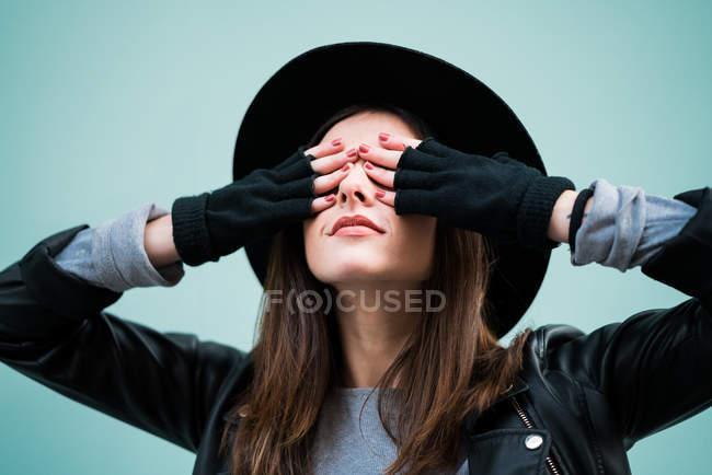 Junge Frau geschlossen Augen mit Händen — Stockfoto