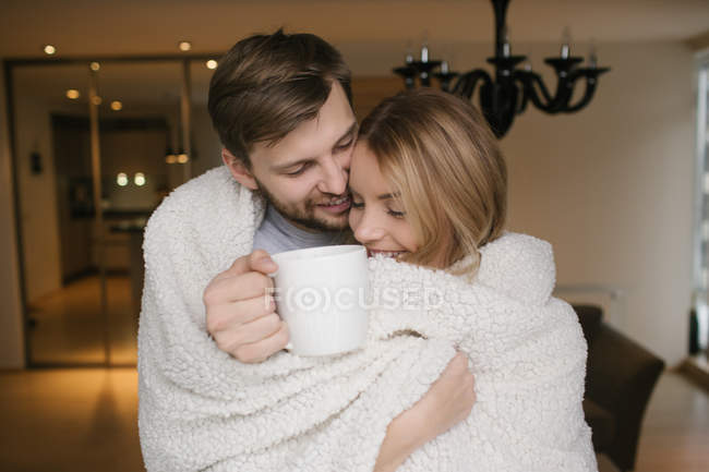 Couple hugging covered with plaid — Stock Photo