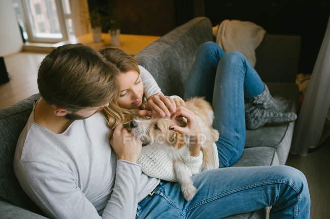 Пара гладить собаку на диване — стоковое фото
