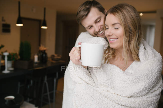 Pair with big mug covered with rug — Stock Photo