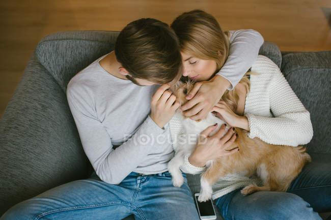 Paar streichelt Hund auf Sofa — Stockfoto