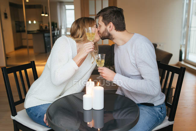 Pair kissing and holding wine glasses — Stock Photo