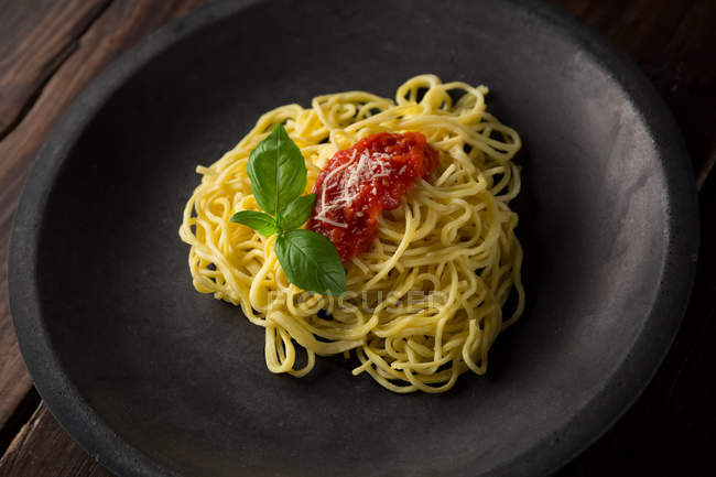 Spaghetti avec sauce et basilic sur plaque — Photo de stock