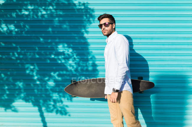Young man in sunglasses holding skateboard — Stock Photo