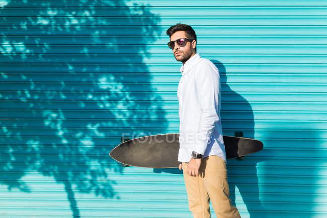 Joven con gafas de sol sosteniendo monopatín - foto de stock