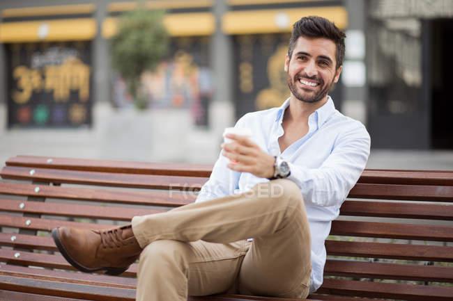 Joven sentado en un banco de madera - foto de stock