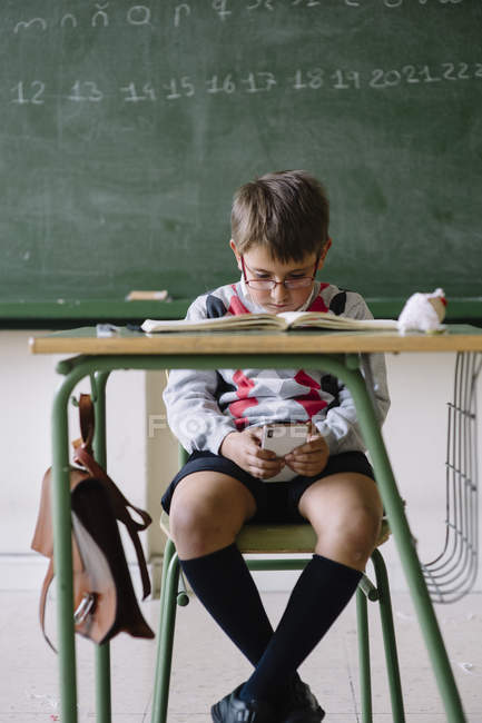 Young boy browsing phone at desk — Stock Photo