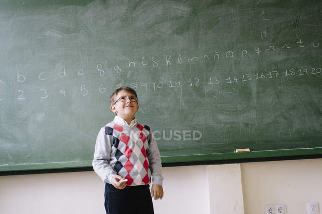 Criança em pé no quadro negro na sala de aula — Fotografia de Stock