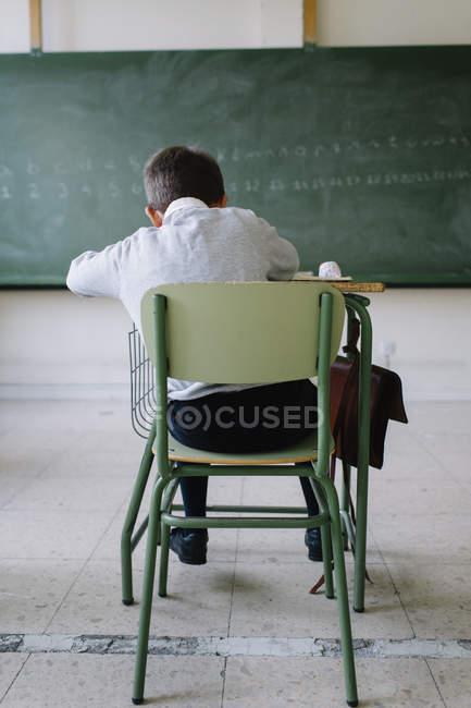 Школяр на столі в класі — стокове фото