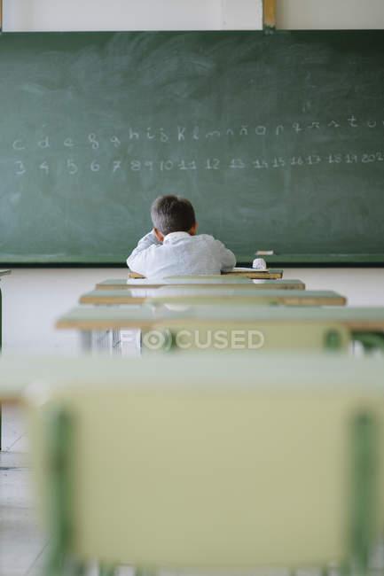 Lycéen au pupitre dans la salle de classe — Photo de stock