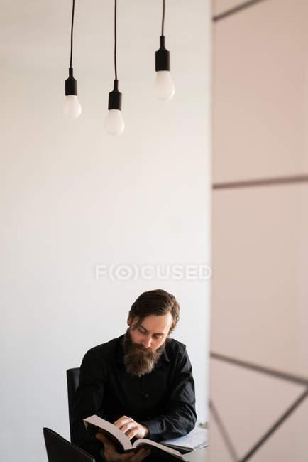 Man reading book at table — Stock Photo
